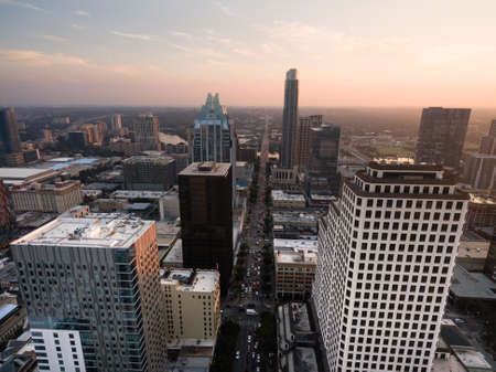People exit downtown Austin as the sun hits the horizon through a maze of tall buildings Stock Photo