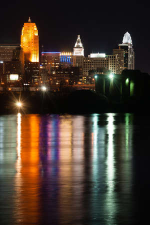 A few buildings light up at night in downtown Cincinnati behind the Ohio River