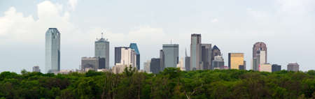 A lush green beltway appears in front of the urban landscape of Houston, TX USA Editorial