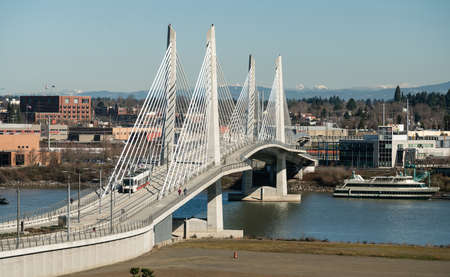 Its a clear day in Portland Oregon at Tilikum Crossing as people traverse the river with the Cascade Mountain Range Stock Photo