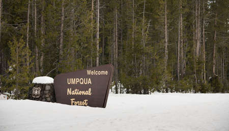 Fresh snow covering the boundary marker sign entering Umpqua National Forest Oregon Stockfoto