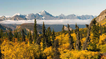 Mountains in the Chugach Range stand above the clouds rising from the Valley in Alaska North America