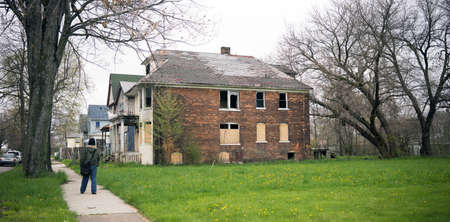 Detroit Michigan boarded up abandoned houses dot the landscape person walking downt the street
