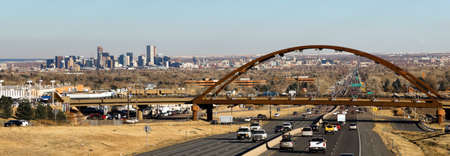 Automobile Traffic passes under a bridge that carries trains for public transit in the Denver Metro area