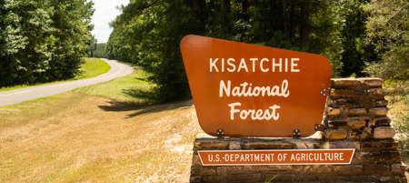 Two lane road passes entrance sign to Kisatchie National Forest