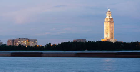 Horizontal composition covering the Mississippi River waterfront barge traffic and the State Capitol of Louisiana at Baton Rouge 新聞圖片