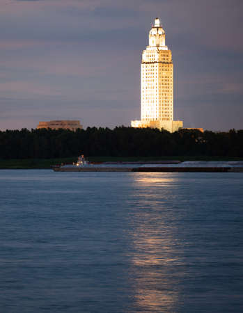 Vertical composition covering the Mississippi River waterfront barge traffic and the State Capitol of Louisiana at Baton Rouge