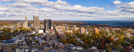The Sun breaks through clouds hitting and illuminating the urban core of New Rochelle New York Reklamní fotografie