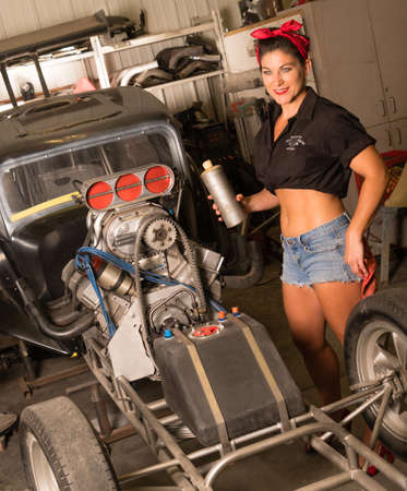 Smiling woman in shorts and belly shirt stands by race car in production