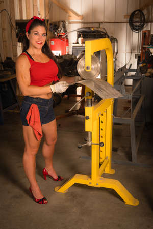 Woman smiling looks at the camera while working a piece of sheet metal in the shop