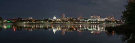The long collection of buildings in the downtown urban core of Harrisburg Pennsylvania reflect in the riverfront