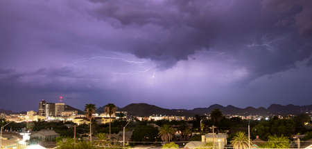 Purple Blue light illuminates the sky over the buildings homes and hills around Tucson Arizona
