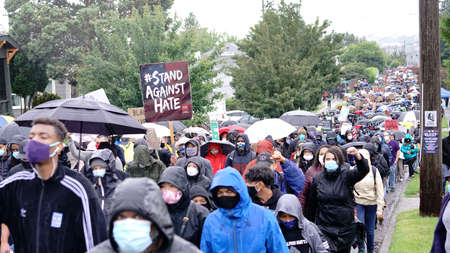 Silent protesters march in the rain through neighborhoods in Seattle calling attention to the Black Lives Matter Movement and Police Brutality Redakční