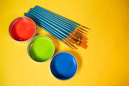 Primary colors in acrylic paint in metal tins still life art supply  and brushes Reklamní fotografie