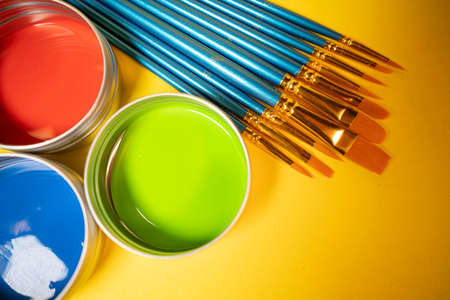 Red Green and Blue Paint Cans on Yellow Background With Brushes