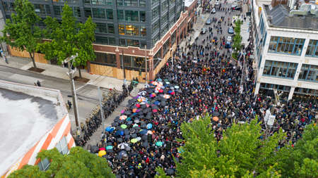 A mob assembles with umbrellas to face off with police in Capital Hill Seattle
