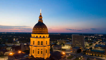 The copper dome shines in the urban area at the capitol building of Topeka Kansas