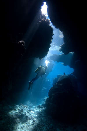 SCUBA diver in a cave with sunbeams Stock Photo