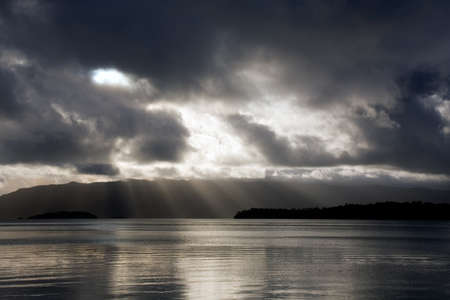 Sunbeams through the clouds, shining on still water, just prior to a tropical storm