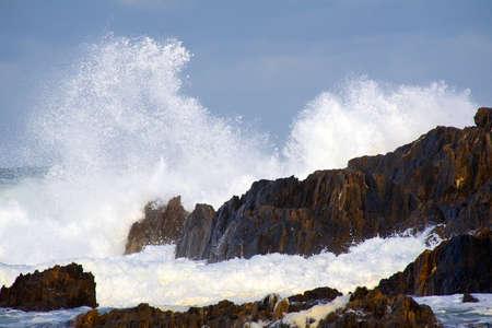 wild surf hitting rocks on the shore
