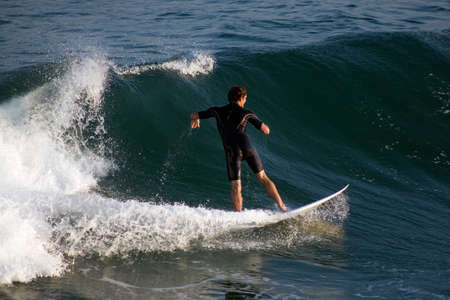 a young male surfer catching a wave Stock Photo
