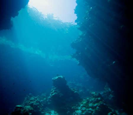 shining through: raggi del sole splende attraverso un buco nel tetto di una grotta sottomarina.