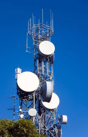 a communication tower silhouetted against blue sky. There are large dishes at the front suitable to add copy or your logo Stock Photo