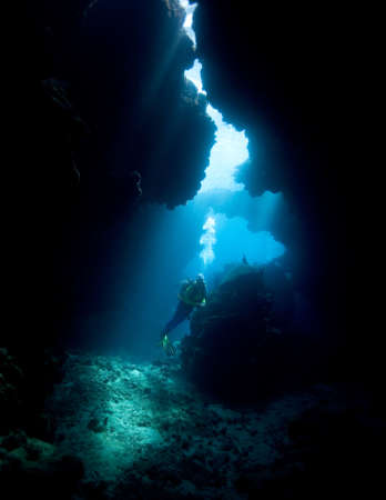 a female scuba diver in an underwater cave with sunbeams Stock Photo