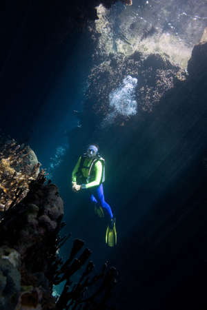 a pretty female scuba diver in a cave with sunbeams