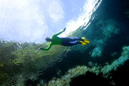 snorkelling: a pretty girl, snorkelling. Taken from underwater, there is a reflection of the sky, reef edge and trees Stock Photo