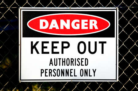 a red, white and black danger sign attached to a wire fence Stock Photo