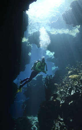 a female scuba diver in an underwater cave with sunbeams shining through the water photo