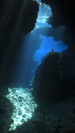sunbeams shining through an underwater cave Stock Photo