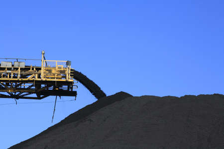 coal mining: a large yellow conveyor belt carrying coal and emptying onto a huge pile.