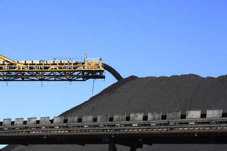 conveyor belts: a large yellow conveyor belt carrying coal and emptying onto a huge pile.