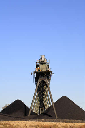 machinery space: Coal Mining Conveyor Belt and piles of coal with a blue sky background. Australia