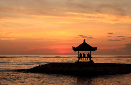 sanur: A pagoda on Sanur Beach, Bali, at dawn. There are threee people waiting to see the sun rise.