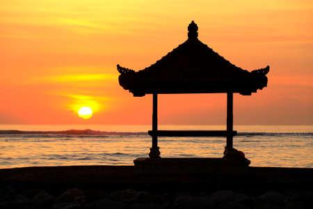 sanur: A Balinese Pagoda on the beach at Sanur. The sun is rising over the ocean. Bali, Indonesia