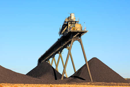 Coal Mining Conveyor Belt and piles of coal with a blue sky background. Australia
