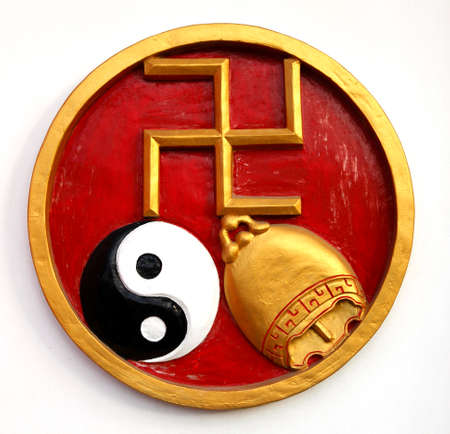 buddhist's: A wall decoration in Bali, with a golden swastika, a ying yang and a golden bell. This is a religious symbol of good luck.