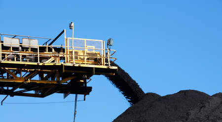 Yellow Coal Conveyor belt carrying coal and pouring onto a pile