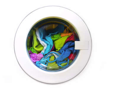 Close-up on a washing machine with clean colorful clothes