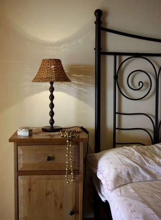 bedside: Detalle de la cama y la mesita de luz con l�mpara.  Foto de archivo