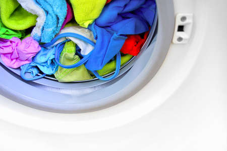 Close-up on a washing machine with clean colorful clothes photo