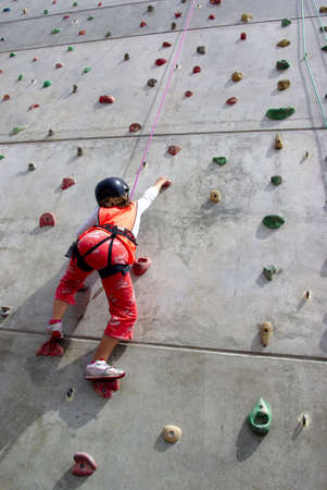 climbing wall: Youngsters effort in climbing a wall to reach the top.