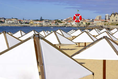 sunshades: Calm beach scene with white sunshades in an early morning Summer day Stock Photo