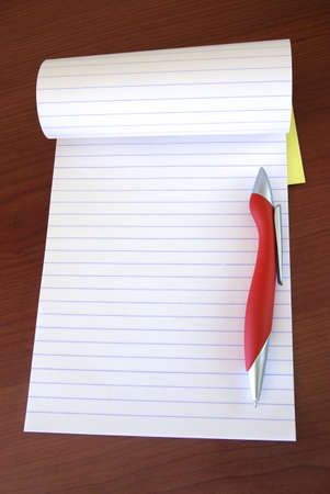 Opened notebook and red pen over a wooden desk Stock Photo - 2425742