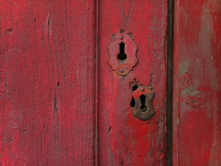 Rusty old wooden door painted in red, with metalic keyhole.