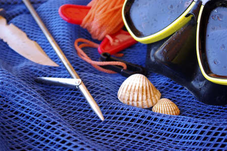 Details of scuba-diving and spear-fishing gear over a blue fishing net bag photo