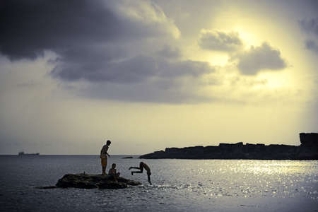 sky dive: Peaceful beach, cloudy sky and silhouettes of kids diving Stock Photo
